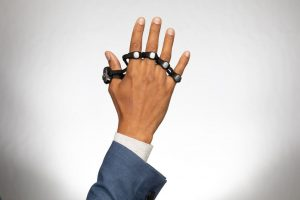 Tap Strap 2 worn on right hand.  Rings on each finger track finger movements and convert them into keystrokes.
