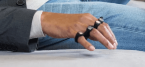 Picture of the Tap Strap 2 typing device, worn around the fingers and thumb of the right hand. The hand is suspended above a chair surface, ready to type by tapping fingers to match specific letter codes.
