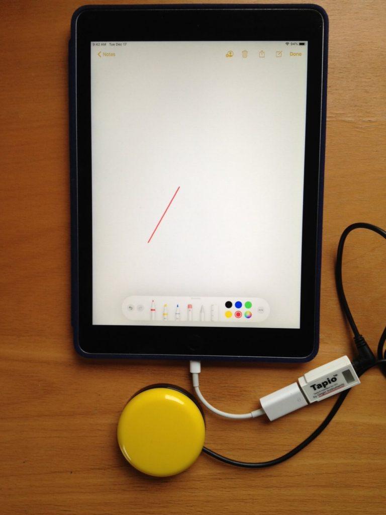 Photo of iPad, round yellow switch, and Tapio switch interface