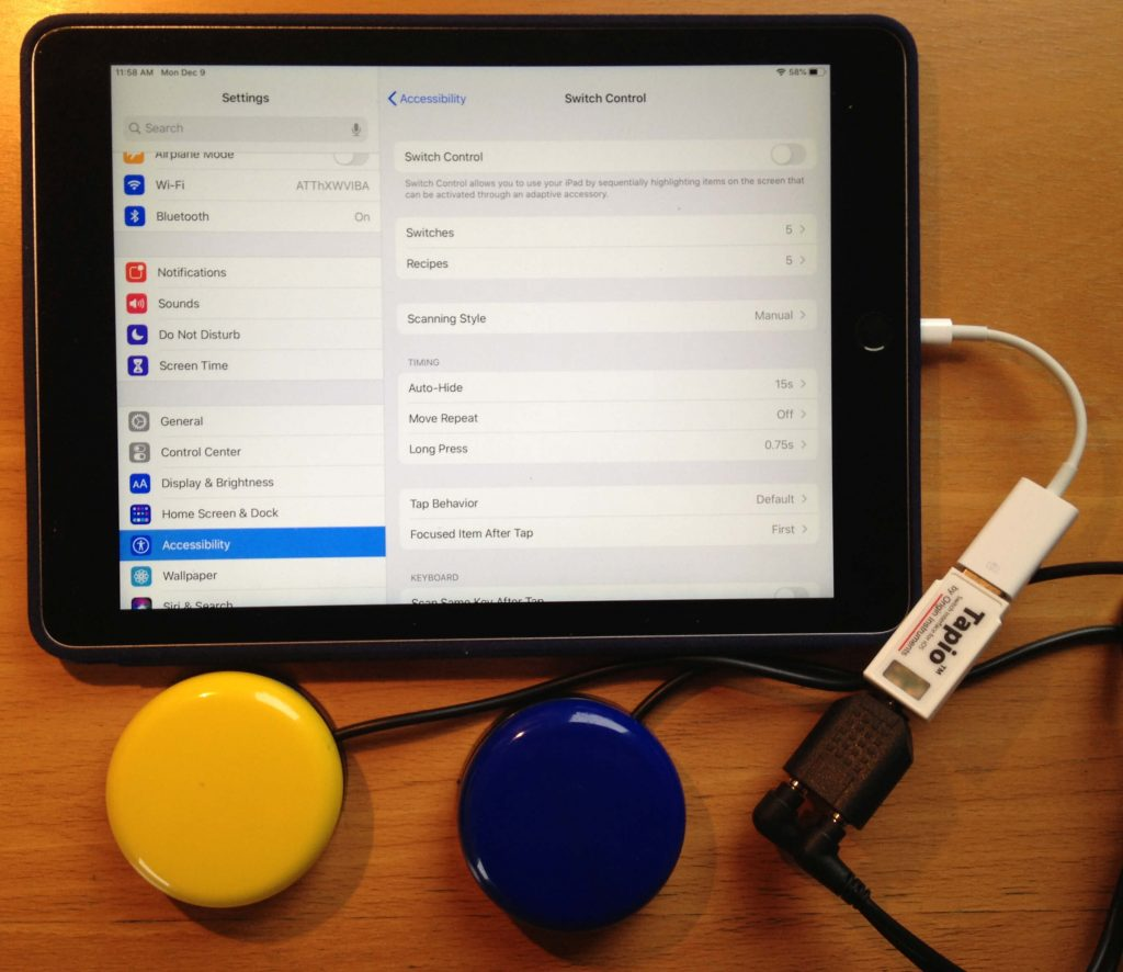 Picture of an iPad with two round switches connected to it via a Tapio switch interface. The screen shows the Accessibility Switch Control settings.