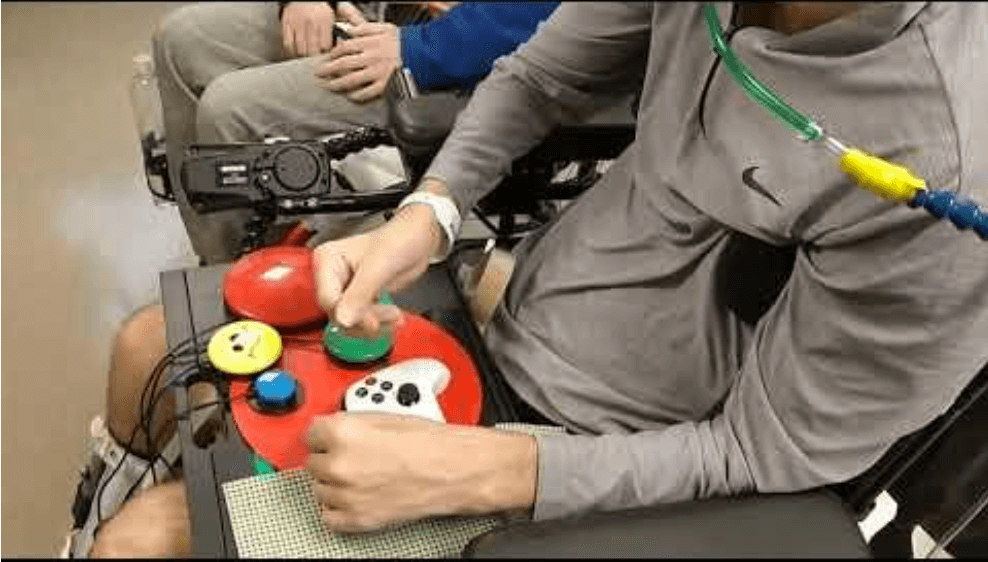 Photo of a person in a wheelchair using switches and an xbox game controller to play games with a friend.