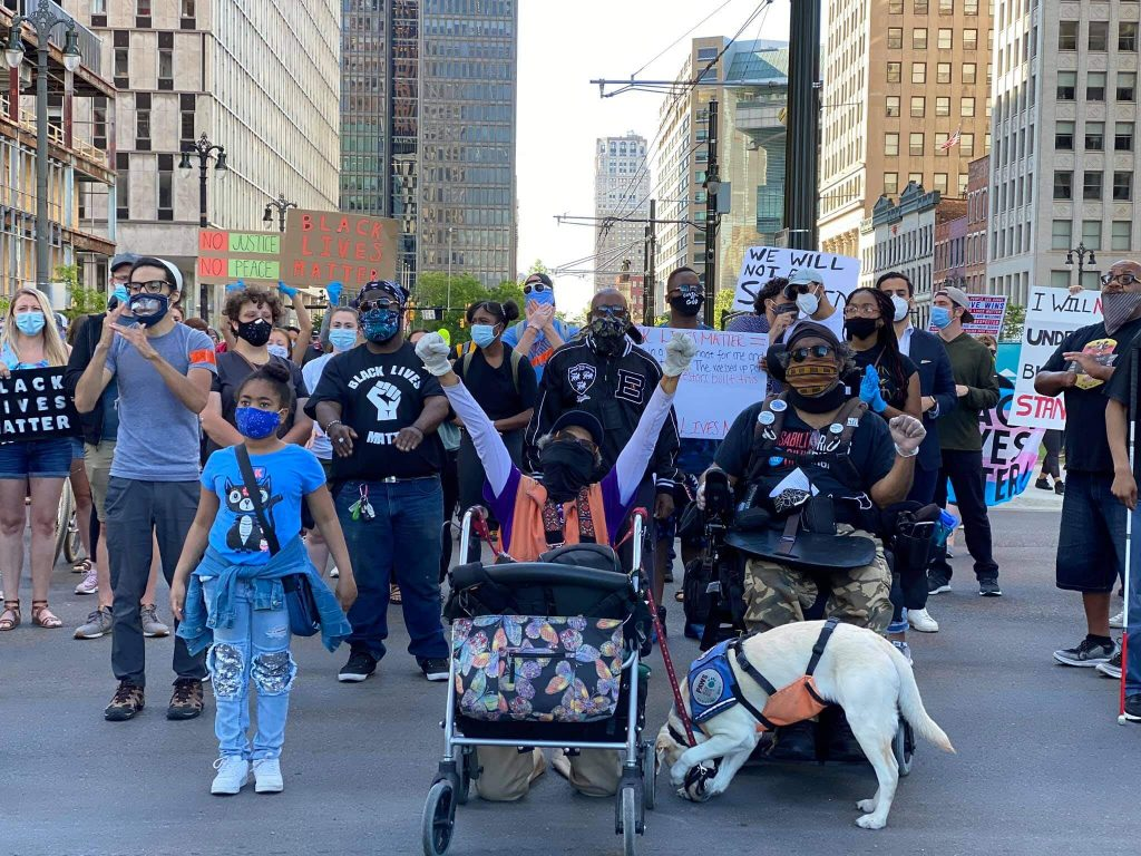 Photograph of a group of people marching for justice in Detroit. Some people are using wheelchairs, others are signing. Black Disabled Lives Matter.